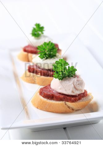 Three salami and cream gulps on a white tray decorated with parsley