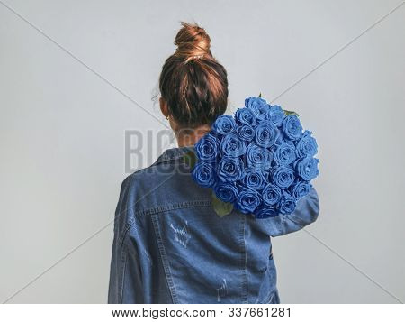Back View Of Young Woman In Denim Jacket Holding Bunch Of Classic Blue Roses On Shoulder. Girl With