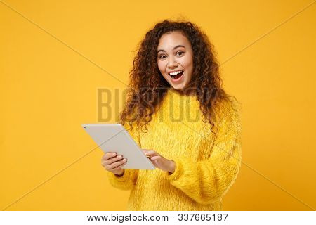 Excited Young African American Girl In Fur Sweater Posing Isolated On Yellow Orange Background In St
