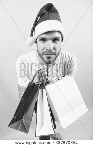 Man Shopper In Santa Hat With Paperbags. New Year, Xmas Presents. Macho Hold Shopping Bags On Orange