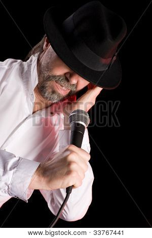 Popular singer performs American jazz blues. Focus on the microphone.