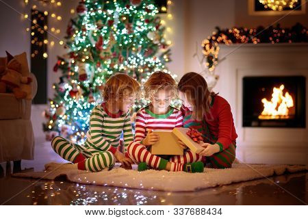 Children At Christmas Tree And Fireplace On Xmas Eve. Family With Kids Celebrating Christmas At Home