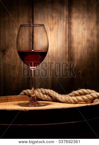 Still Life With A Glass Of Red Wine. A Glass Of Red Wine Standing On An Old Barrel Against The Backg