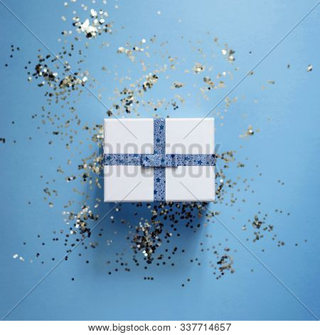 Present Or Gift In A White Box With Blue Ribbon On Blue Trendy Background With Silver Confetti Close