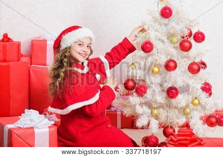 Christmas eve concept. Join christmas celebration. Girl smiling adorable santa claus sit near christmas tree. Kid decorating christmas tree. Cherished holiday activity. Child enjoy family tradition poster