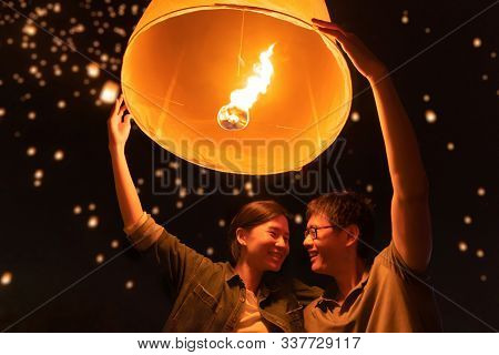 A Couple Release Sky Floating Lanterns Or Lamp To Worship Buddha's Relics At Night. Traditional Fest