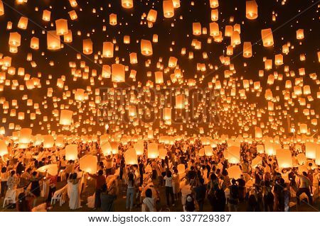 Thai People Release Sky Floating Lanterns Or Lamp To Worship Buddha's Relics At Night. Traditional F