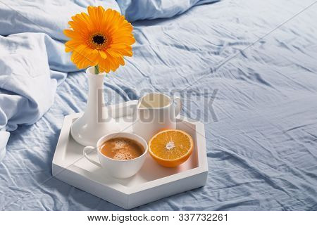 Tray With Coffee, Milk, Orange And Yellow Flower In A Vase On It Standing On The Bed.