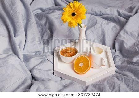 Coffee, Half Of Orange, Milk And Gerbara Flower In A Vase Standing On The Bed.