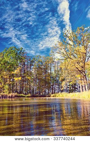 Vertical Photo With Small Lake. Photo Is Captured In Autumn With Several Trees Around With Colorful