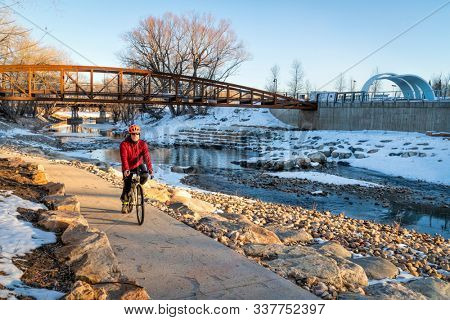 senior male cyclist is riding a bike in winter sunset scenery - Poudre River Trail in Fort Collins, Colorado at downtown whitewater park, recreation and commuting concept