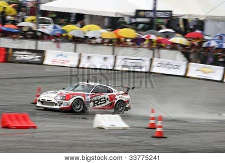 KUALA LUMPUR - MAY 20: Max Orido (red/white RSR) accelerates on the wet tarmac during the Formula Drift 2012 Asia Round 1 on May 20, 2012 in Speedcity, Malaysia. He emerged second in this competition.