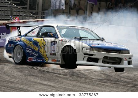 KUALA LUMPUR - MAY 20: Malaysia's Hanizam Hamzah (car #72) leaves a trail of smoke as he drifts in this qualifying run at the Formula Drift 2012 Asia Round 1 on May 20, 2012 in Speedcity, Malaysia.