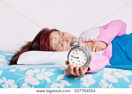 Young Woman Sleeping In Bed, Holding An Alarm Clock. Young Woman Fallen Asleep With Alarm Clock In H