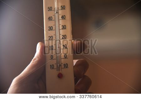 Hand With A White Plastic Mercury Thermometer Shows The Temperature In The Room