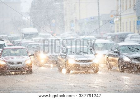 Cars With Headlights On Go On The Road Under Snow In The Winter