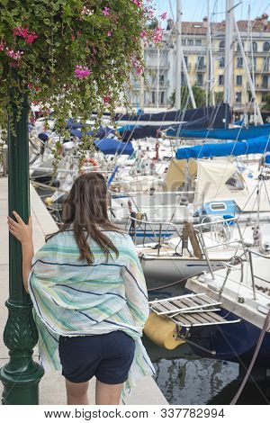 Tourist Woman Resting In A Famous Resort Destination With Yachts In A Sea Port Leaning On Street Lig