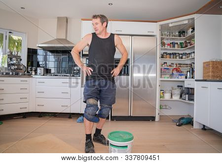 Tauranga New Zealand - November 4 2019; Tradesman Laying New Wooden Floor In Home Standing In Kitche