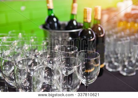 Red Wine Bottle In Ice Bucket And Wine Glass On The Table Background / Champagne Glass For Celebrati