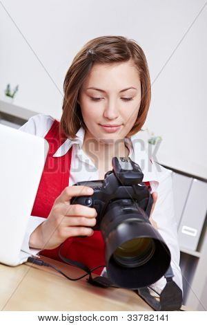 Female photographer in studio checking images on DSLR camera display