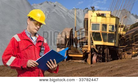 A foreman in a mining site, checking the logs in a blue folder, with a huge wheel digger in the background