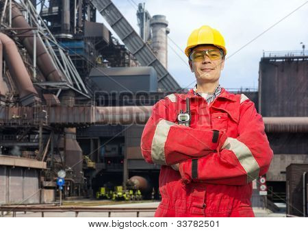 Factory worker posing in front of a blast furnace, wearing safety gear, including a hard hat, goggles and fire retardant coveralls poster