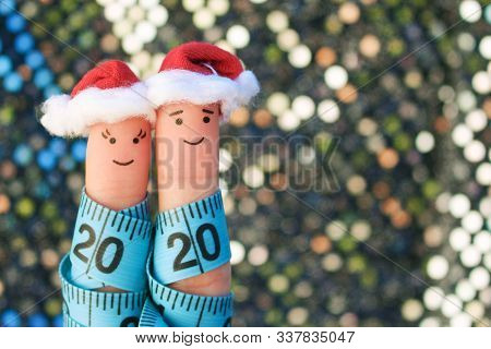Fingers Art Of Couple Celebrates Christmas. Concept Of Man And Woman Laughing In New Year Hats. Meas