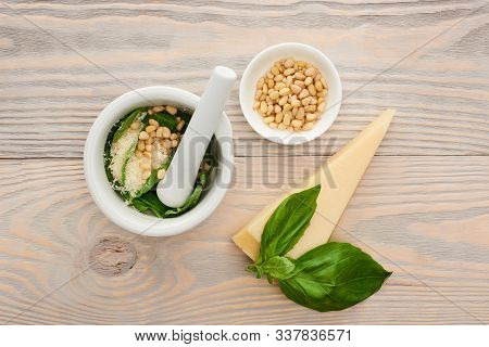 Top View Of Pesto Sauce Raw Ingredients In Pounder On Wooden Table