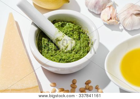 Close Up View Of Pesto Sauce In Pounder Near Ingredients On White Background