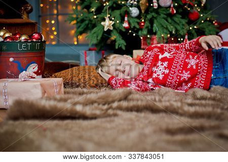 A Child Sleeps On Christmas Eve Under A Decorated Christmas Tree Waiting For A Gift. Family Celebrat