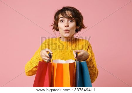 Amazed Young Brunette Woman Girl In Yellow Sweater Posing Isolated On Pink Wall Background In Studio