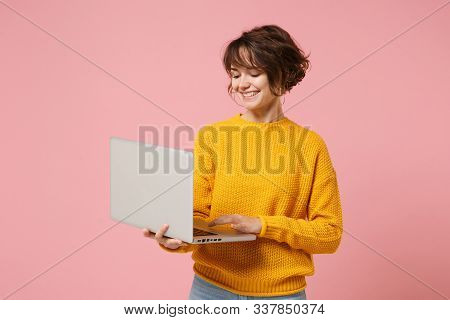 Smiling Young Brunette Woman Girl In Yellow Sweater Posing Isolated On Pastel Pink Background Studio