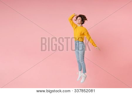 Smiling Young Brunette Woman Girl In Yellow Sweater Posing Isolated On Pastel Pink Background. Peopl