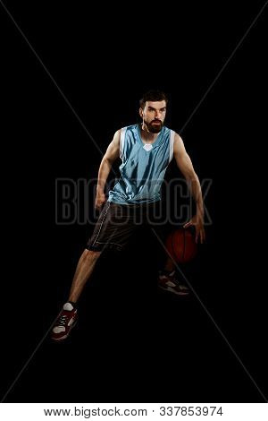 Man Dribbling Ball Between Legs. Concentrated Basketball Player