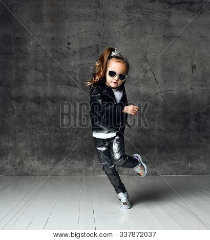 Cool Frolic Kid Girl In Leather Jacket, Jeans And Sunglasses Is Having Fun Modern Dancing Playing Ru