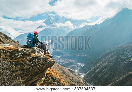 Young Hiker Backpacker Female Sitting On The Cliff Edge And Enjoying Ama Dablam 6,812m Peak View Dur