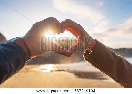 Closeup Of Couple Hands Making Heart Shape In The Beach, In Autumn Season. Happy Couple In Love .