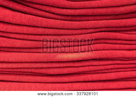Clothes Stacked Close-up, Fabric Texture, Bright Colors, Neat Red Stacks