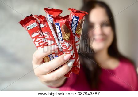 Kharkov, Ukraine - October 21, 2019: A Young Caucasian Brunette Girl Shows Many Kit Kat Chocolate Ba