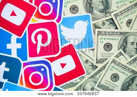 Many Hundred Dollars Bills With Printed Logo Of Social Networks. Facebook Instagram Youtube Tumblr T