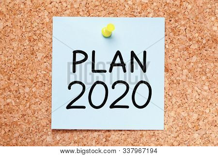 Text Plan For Year 2020 Handwritten On Blue Sticky Note Pinned On Cork Bulletin Board.