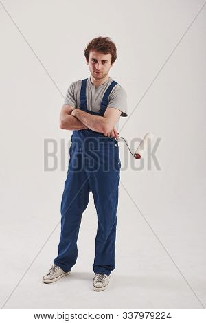 Here We Go. Man In Blue Uniform Stands Against White Background In The Studio.