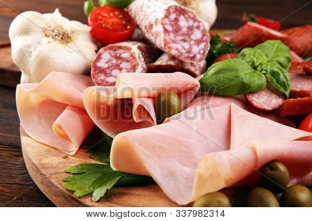 Food Tray With Delicious Salami, Pieces Of Sliced Prosciutto Crudo, Sausage And Basil. Meat Platter