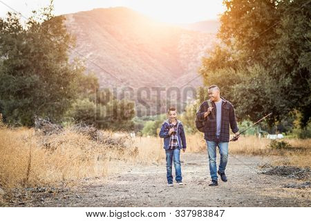 Mixed Race Father And Son Outdoors Walking With Fishing Poles.