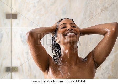 Young woman washing hair in shower at luxury spa. Woman washing her curly hair with shampoo and a lot of lather. Carefree black girl taking a long hot shower washing her hair in a modern bathroom.