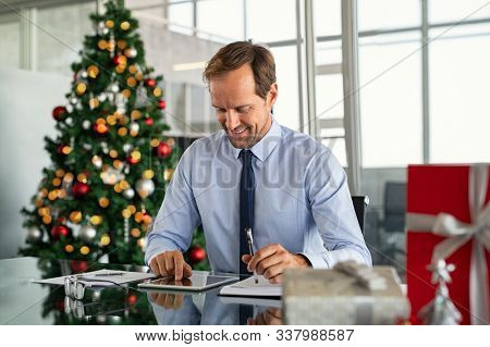 Mature business man working with xmas present and gift on desk. Successful formal businessman using digital tablet to send an email. Happy entrepreneur working in office during christams holiday.