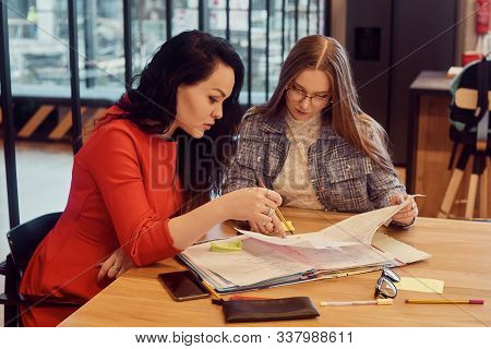 Female Students Do Their Homework Together At The University At The Table. Exchange Of Foreign Stude