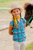 Lovely cowgirl and pony on a ranch poster