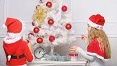 Children decorating christmas tree together. Siblings busy decorating. Boy and girl decorating tree. Cherished holiday activity. Kids in santa hats decorating christmas tree. Family tradition concept poster
