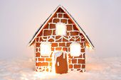 The hand-made eatable gingerbread house with light inside and snow decoration poster